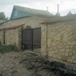 каменный забор с металлическими воротами